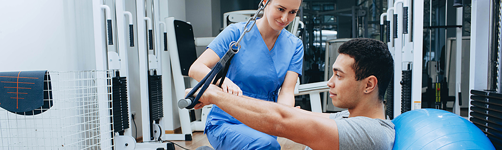 Kinesiologist helping patient exercise
