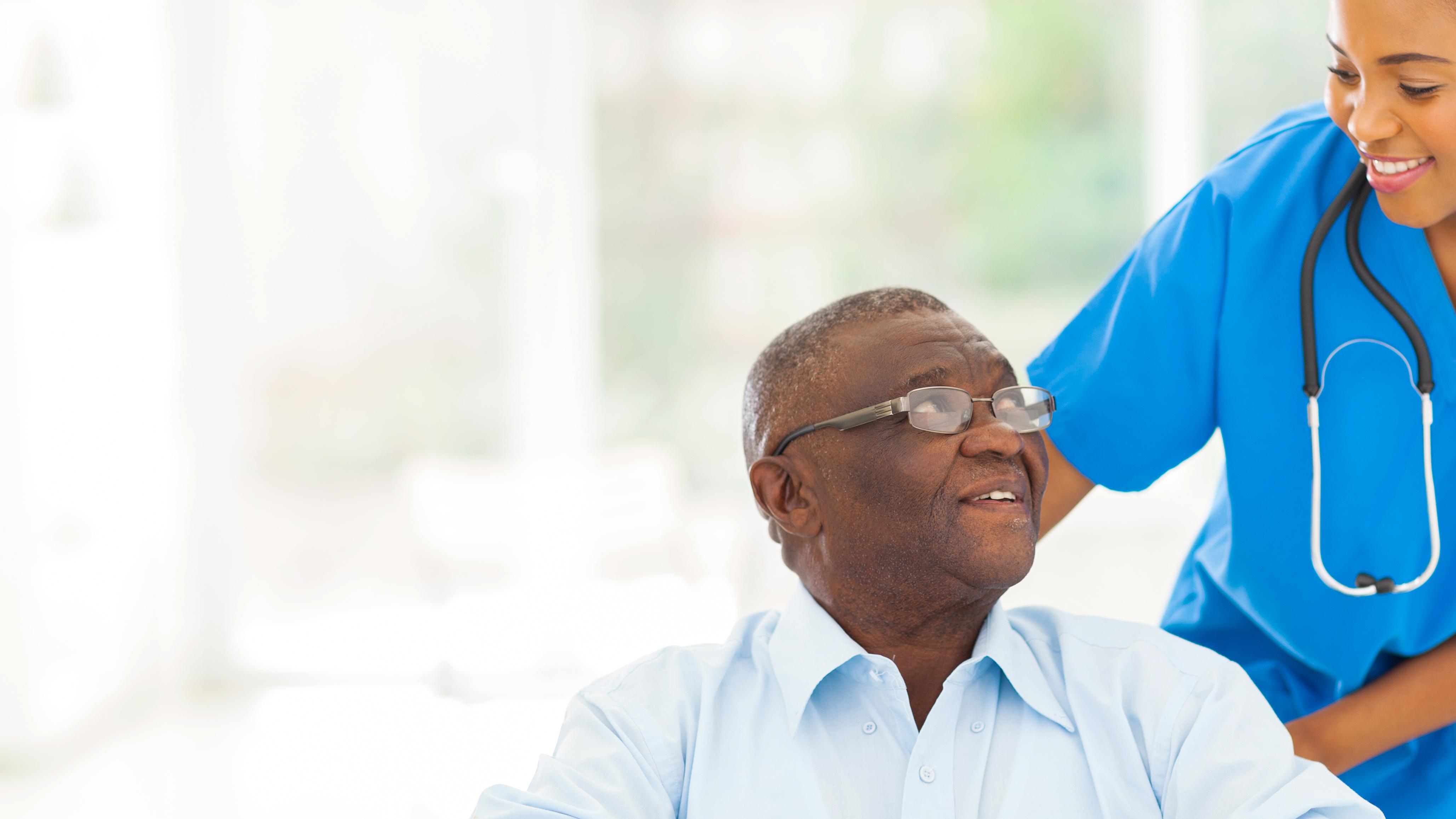 Black female nurse smiling at elderly black man in a wheelchair