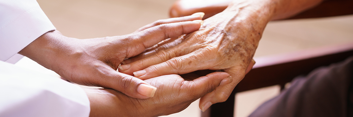 Black doctor holding hand of senior woman