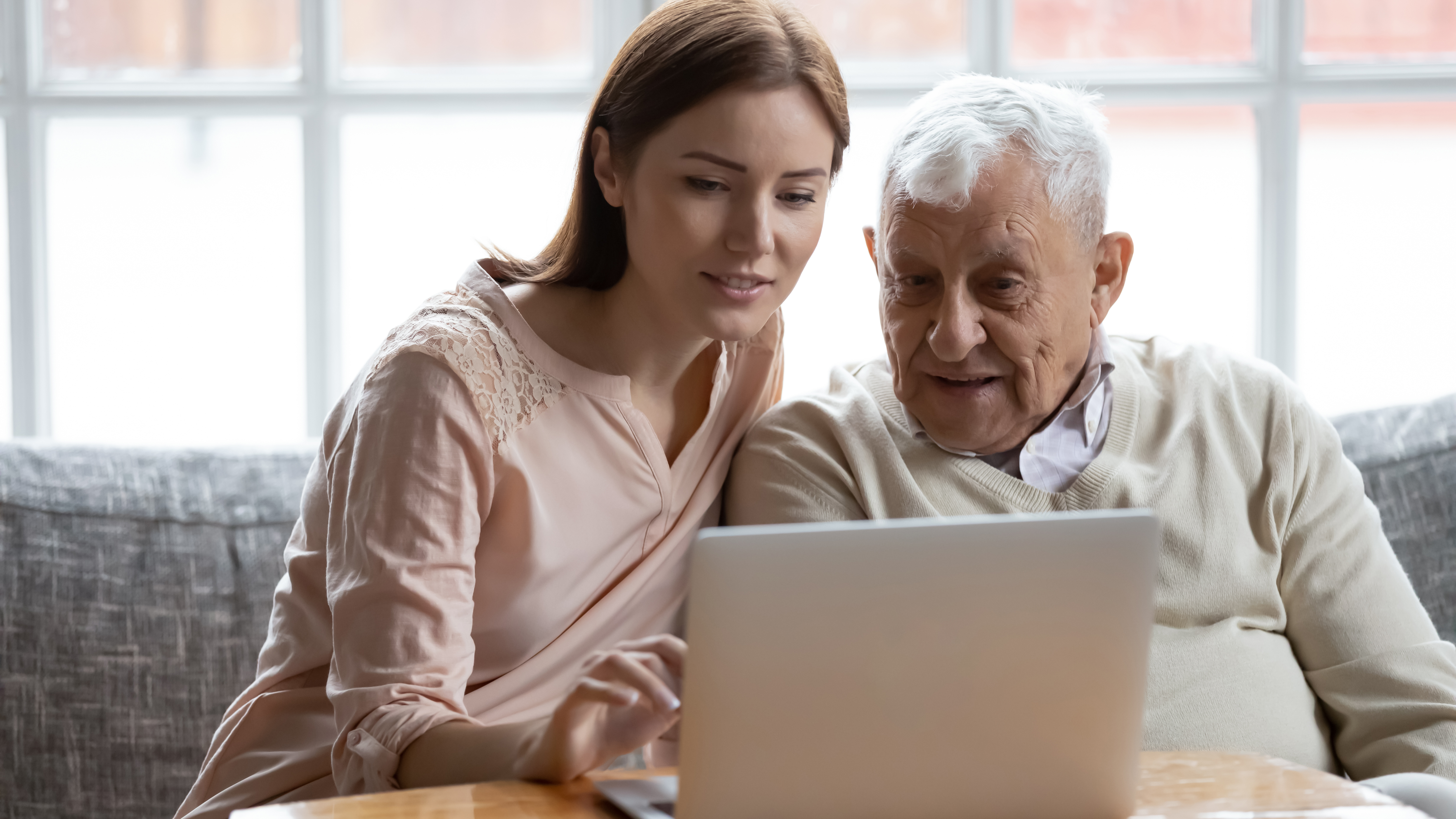 Woman helping an elderly man learn the computer